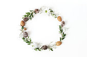 Christmas circle floral composition. Wreath of eucalyptus branches, larch cones, almonds, chrysanthemum and baby's breath flowers on white background, winter wedding design. Flat lay, top view.