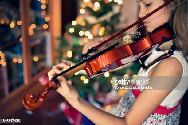 Christmas. Close up of the hands of a girl playing the violin at home in Christmas time.