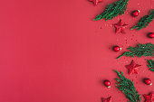 Christmas composition. Christmas red decorations, fir tree branches on red background. Flat lay, top view, copy space