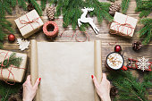 Christmas composition. Female holding empty scroll wishlist for Santa Claus or holiday cheers laid on a wooden table with christmas giftbox and decor. Flat lay, top view, copy space.