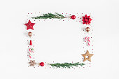 Christmas composition. Frame made of christmas tree branches, red and golden decorations on white background. Flat lay, top view, copy space