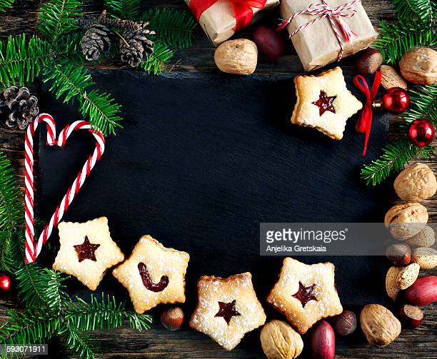 Christmas cookies, nuts and fir branches on wooden