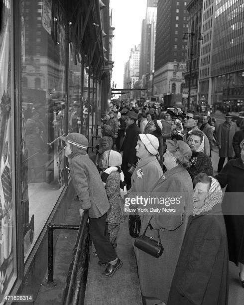 Christmas crowds along 34th St with their noses pressed against the glass children window shop with their family at Macy's in Manhattan