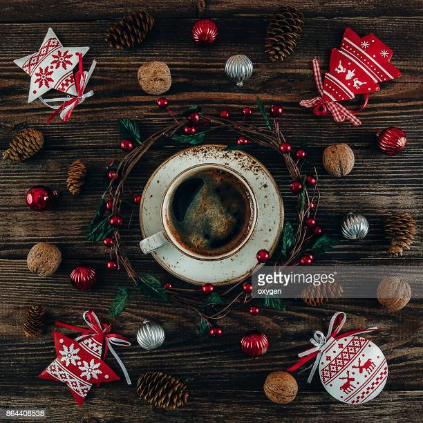 Christmas Decor with Cup of Coffee and Wreath on Centre Dark Wooden Background