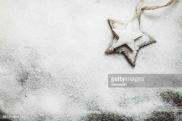 Christmas decoration on wood, wooden stars, artificial snow, copy space