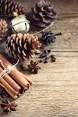 Christmas decoration with cinnamon sticks and star anise, cones, nuts and Christmas ornaments over rustic vintage wooden background, selective focus and copy space