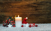 Christmas candle with decoration, red santa cap and small present.