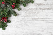 Christmas decoration with fir tree branches on snowy wooden background with copy space.