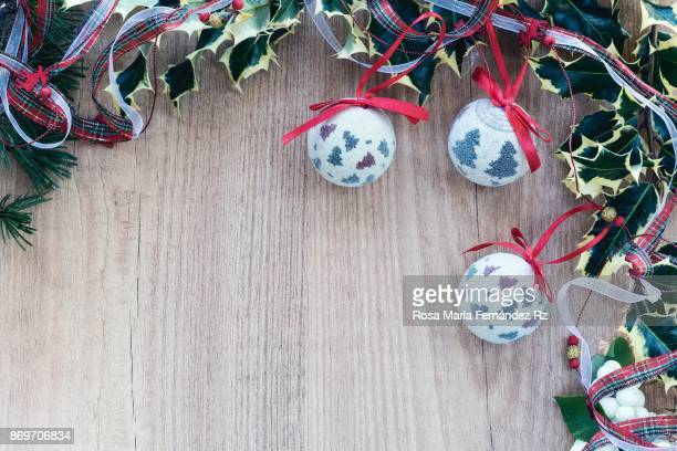 Christmas decorations: Christmas balls with red ribbon, holly leaves and pine cone with copy space on wooden background. Top view