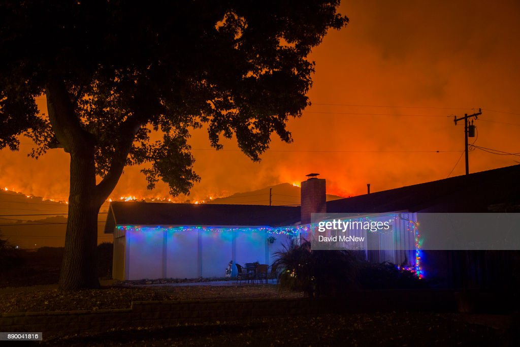 Christmas decorations illuminate a house as the growing Thomas Fire advances toward Santa Barbara County seaside communities on December 10, 2017 in Carpinteria, California. The Thomas Fire has grown to 173,000 acres and destroyed at least 754 structures so far. Strong Santa Ana winds have been feeding major wildfires all week, destroying houses and forcing tens of thousands of people to evacuate.