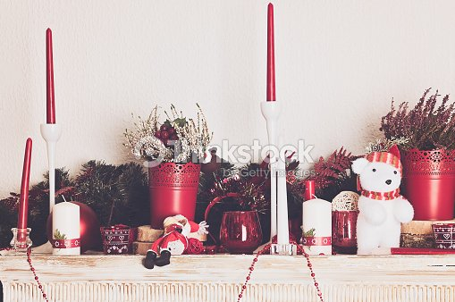 christmas decorations with candles on mantelpiece stock photo