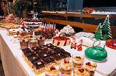 Buffet of Christmas table with different homemade desserts, cakes and sweets