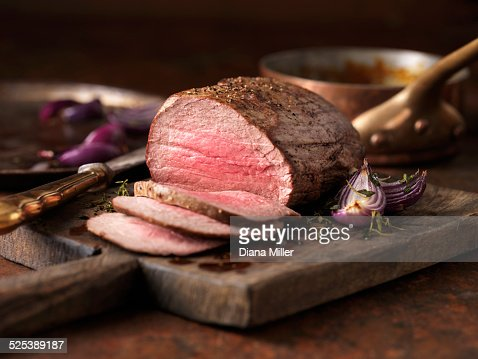 Christmas dinner. Chateaubriand steak cooked with a thick cut from the tenderloin filet, rare medium served with roasted onions, pepper and herbs
