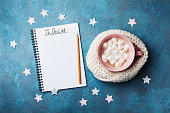 Christmas do list and cup of hot cocoa decorated knitted scarf with marshmallow on vintage turquoise table top view. Flat lay style. Holiday mockup.
