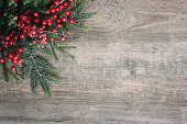 Christmas Evergreen Branches and Berries in Corner Over Rustic Wood Background
