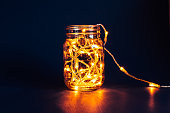 Christmas fairy lights in a mason jar, glowing in the dark, on a blue background.