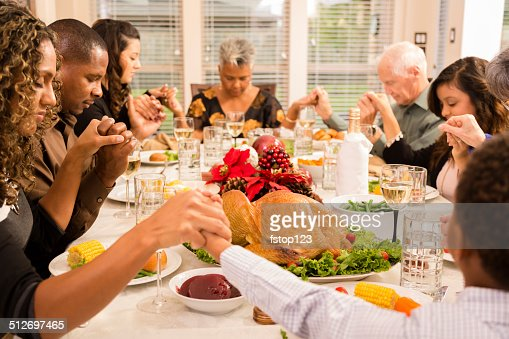 Christmas:  Family prays before eating holiday dinner.