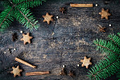 Christmas fir tree with homemade gingerbread cookies stars with cinnamon and anise on old wooden background with space for text. Merry Christmas and Happy New Year. Xmas concept. Top view. Copy space.