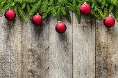 Christmas fir tree with decorations on wooden background. Red ornaments hanging on branches on old wooden boards