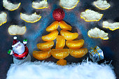 Christmas fir-tree with a santa and a gift in the background of the starry sky. Symbol of the New Year and Christmas