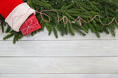 Christmas new year flat lay decor of fir branches, sock and gift on white toned natural wooden plank background texture provence style with copy space for text