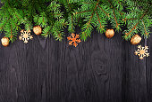 Christmas frame with spruce branches and a golden nut on a black wooden texture background with copy space