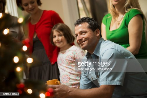 A Christmas gathering, adults and children in a room around a Christmas tree, celebrating together. : Stock Photo