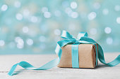 Christmas gift box against turquoise bokeh background. Holiday greeting card.