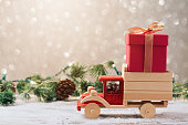 Christmas gift box on toy truck over festive background. Christmas holiday celebration concept