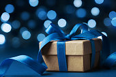 Christmas gift box or present against blue bokeh background. Holiday greeting card. Macro.