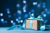 Christmas gift box or present with bow ribbon on magic blue bokeh background. Copy space for greeting card.
