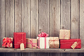 Christmas gift boxes in front of wooden wall with copy space. Retro toned