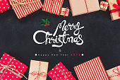 Colorful gift boxes on blackboard background with greeting texts Merry Christmas and Happy New Years 2018
