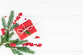 Christmas composition. Christmas gift, fir tree branches and red berries on white background. Flat lay, top view, copy space