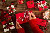 Christmas gift giving - hands wrapping red and white paper christmas gift boxes with decorations on wooden background