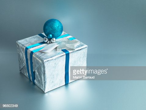 Christmas gift with silver wrapping and blue ribbon : Stock Photo