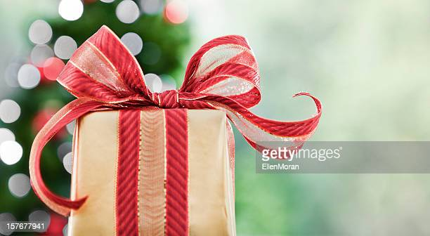 A Christmas gift wrapped in gold with a red bow