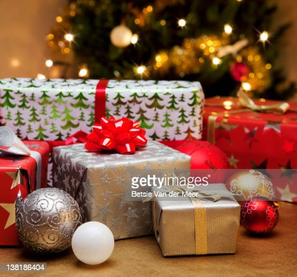 Christmas gifts and baubles in front of tree. : Stock Photo