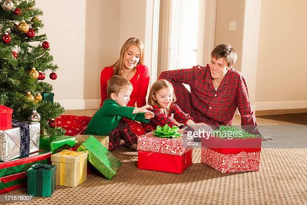 Joven familia abriendo regalos de Navidad en la mañana