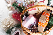 Christmas Gifts in a basket with Candle, balls, pine cones, snowflakes on white Wooden Background. Flat lay