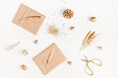 Christmas composition. Christmas gifts, pine cone, golden decorations on white background. Flat lay, top view