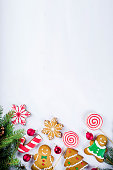 Various traditional colorful sugar glazed christmas gingerbread cookies, on white background top view copy space banner with xmas decorations