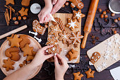 Christmas gingerbread making. Friends decorating freshly baked cookies with icing and confectionery mastic, view from above. Festive food, family culinary, Christmas and New Year traditions concept