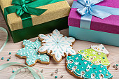Gift boxes with ribbons for Christmas gingerbread, on wooden surface.