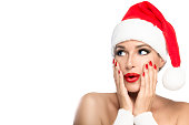 Gorgeous sexy young woman with bare shoulders in a red Santa hat with matching lipstick and manicured nails pouting her lips in a surprised expression, isolated on white with copy space for your Chris