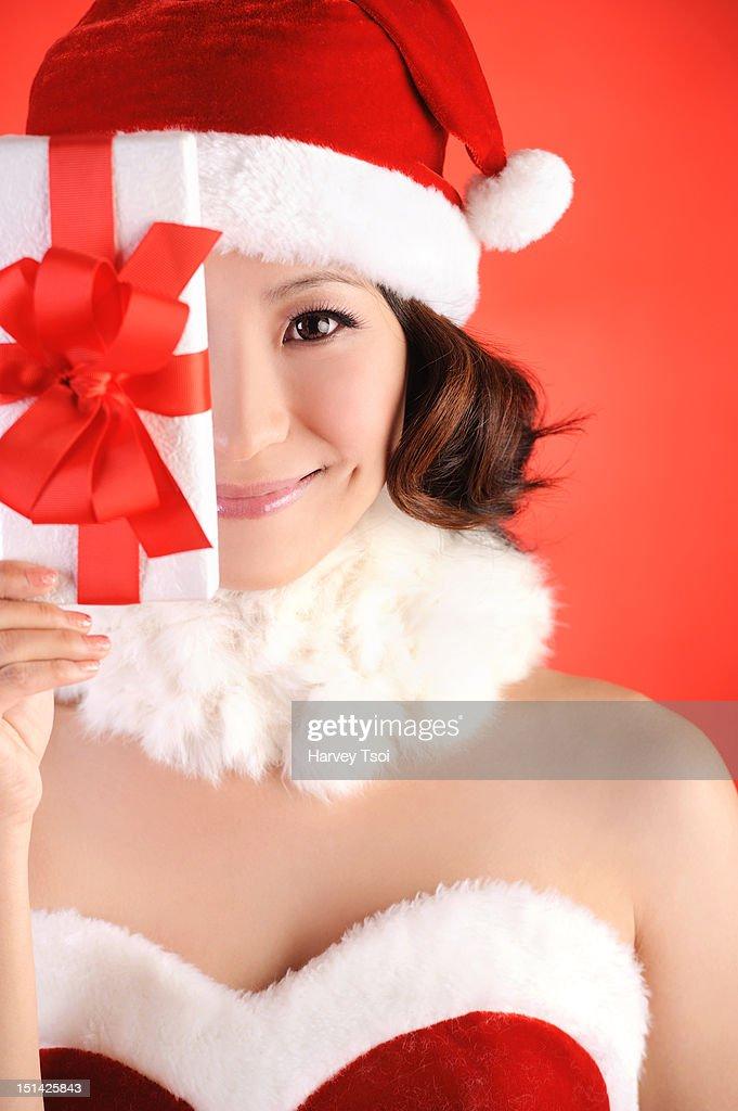 Christmas Girl Holding Gift Up Near Face : Stock Photo