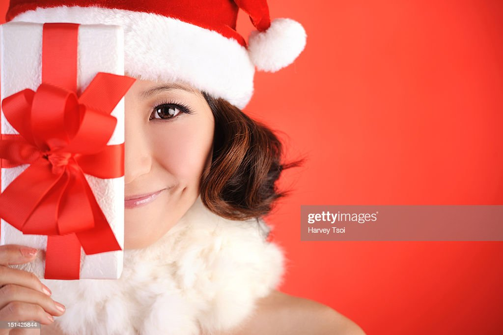 Christmas Girl Holding Gift Up Near Face : Stock Photo