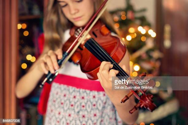 Christmas. Happy little girl playing the violin with the Christmas light in the background.