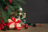 Christmas holiday background. Gifts with a red ribbon, Santa's hat and decor under a Christmas tree on a wooden board. Close up. Copy space on chalkboard.