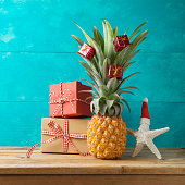 Christmas holiday concept with  pineapple as alternative Christmas tree and gift boxes on wooden table with copy space